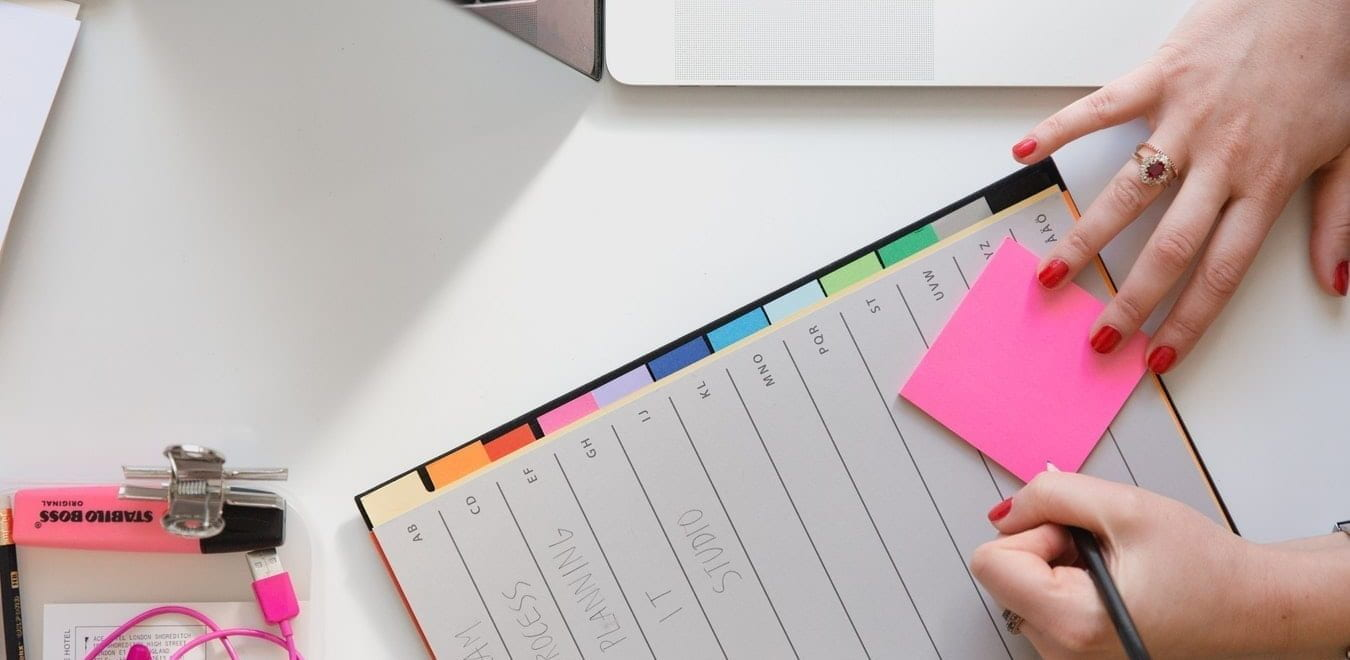 A woman writes in her planner with a pencil