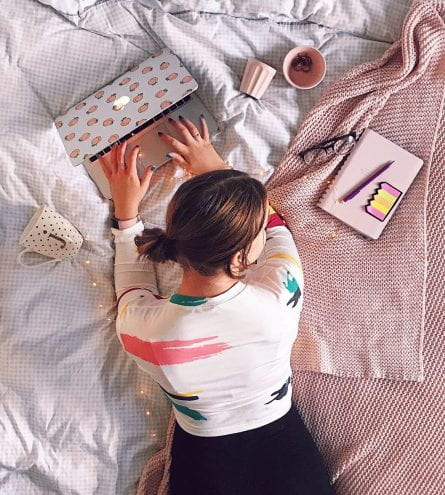 Top down photo of a young woman studying on her bed