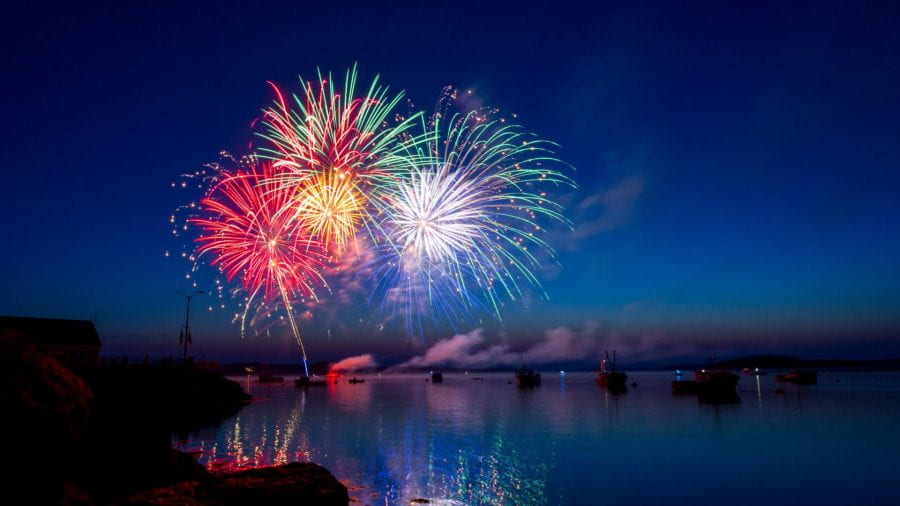 Red, yellow and green fireworks over water