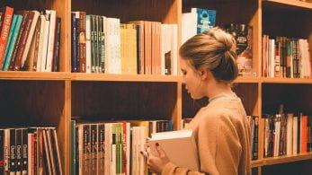 A girl stood in front of a bookshelf full of books, holding a book