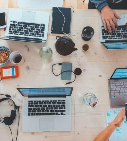 A birds eye view of a table with numerous laptops, phones and other electronics with people's hands using the laptops