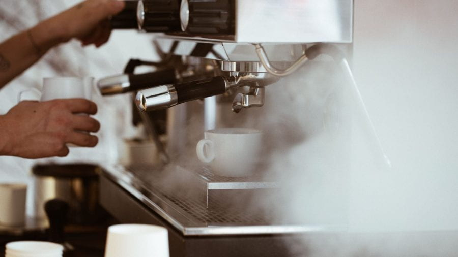 Close up of coffee machine steaming with a man frothing milk