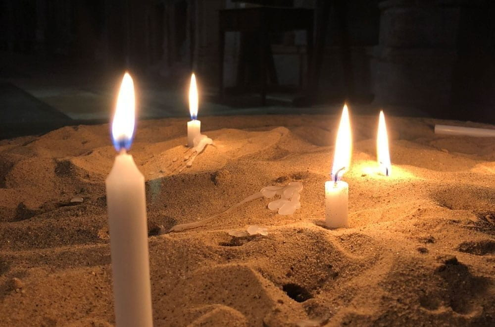 Lit candles placed in sand in Lincoln Cathedral