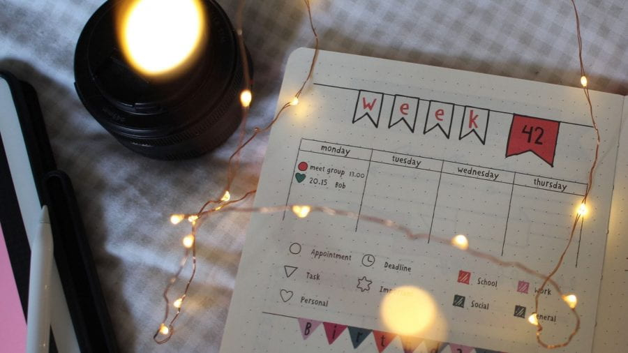 Week planner notebook open on a bed with and iPad and fairy lights