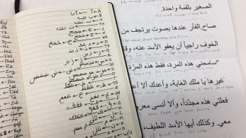 A notebook and a sheet of paper with writing in Aarabic