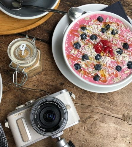 Camera and smoothie bowl in coffee shop
