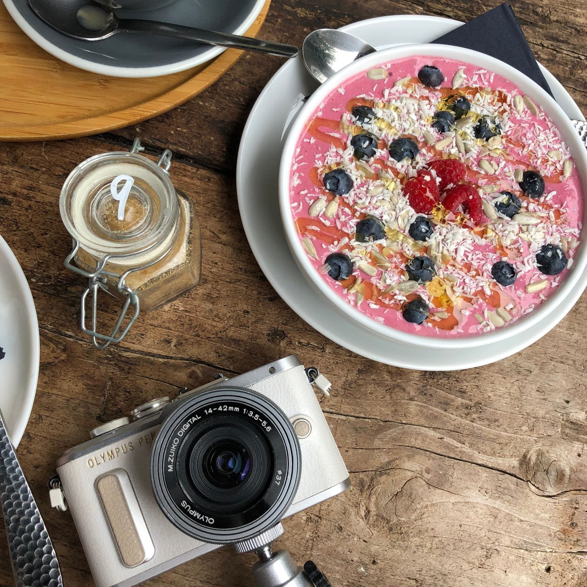 Smoothie bowl and camera in coffee shop