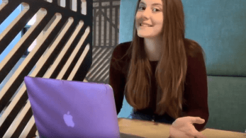 A girl smiling sat at a desk in front of a laptop