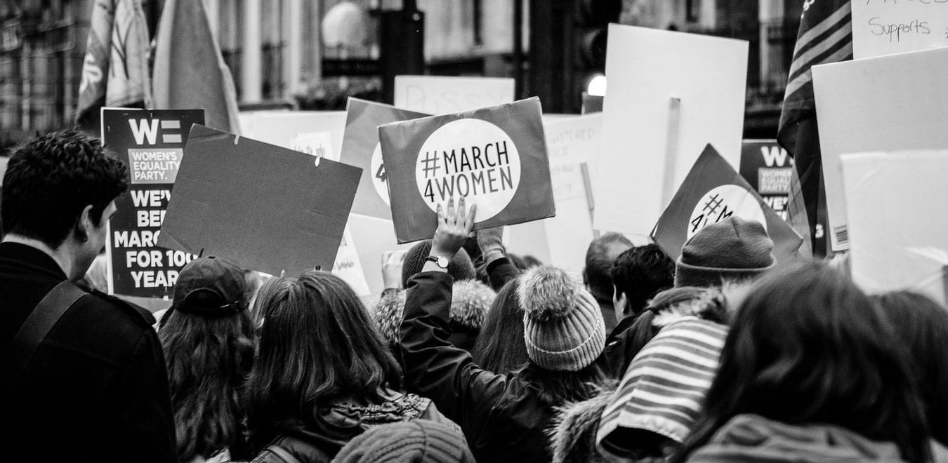 Black & white photograph of a #March4Women with placards in the air