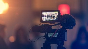 A camera filming a scene with a blurred background