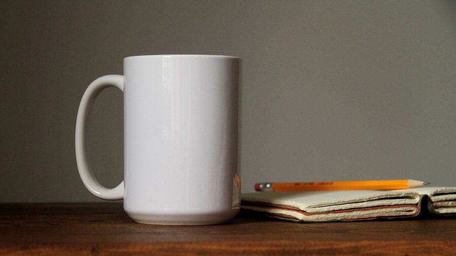 A mug on a table next to a notebook and pencil