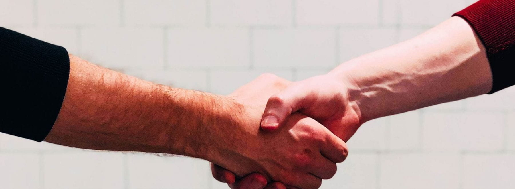 Two men shaking hands in front of a white wall