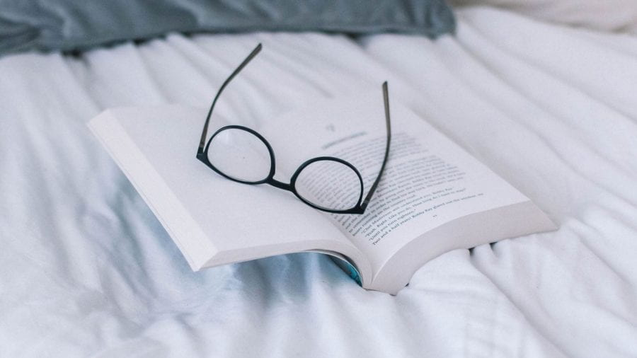 A pair of glasses lying on a book on top of a bed