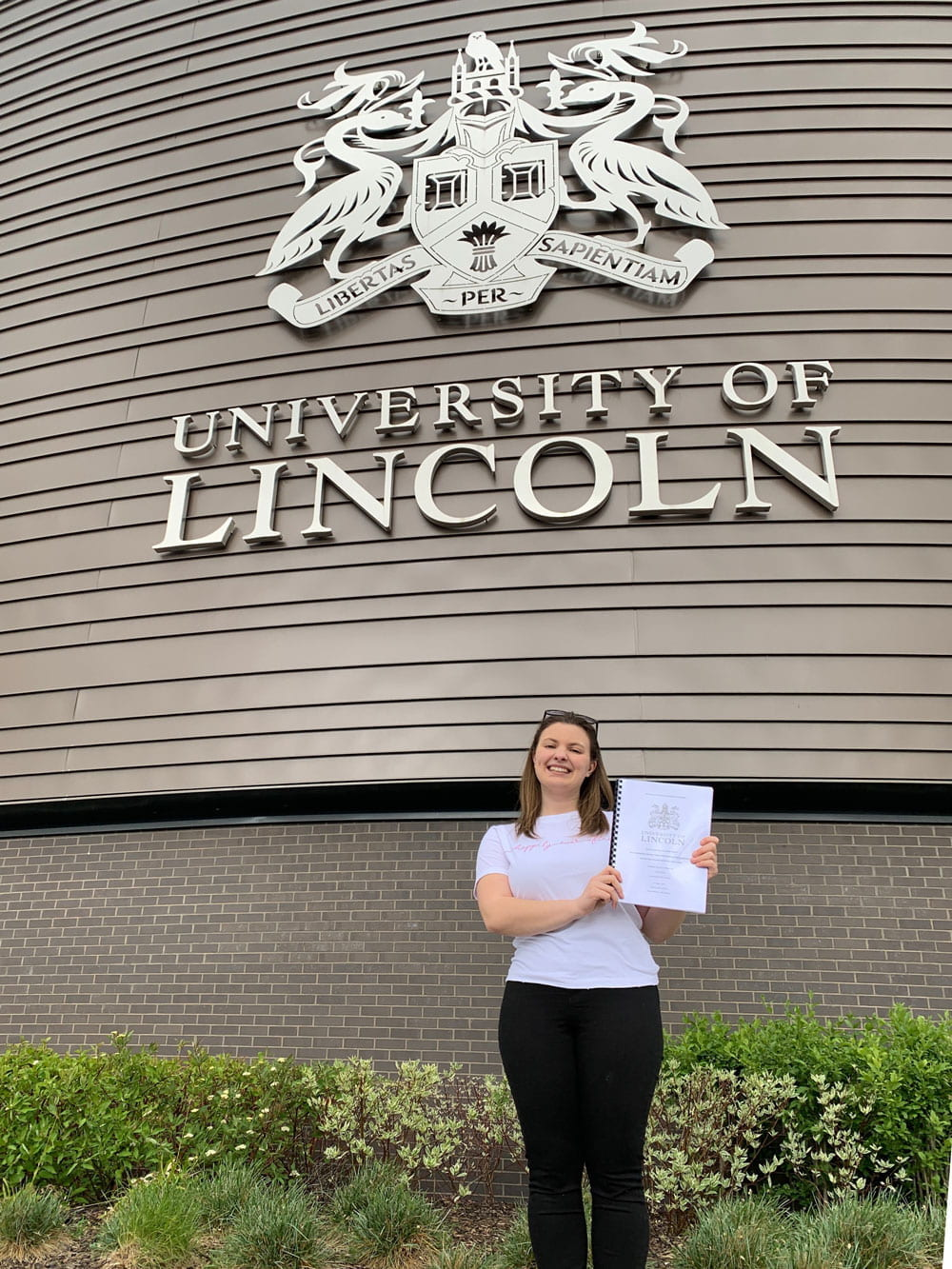 A young woman holding a dissertation and smiling in front of the University of Lincoln logo on a building
