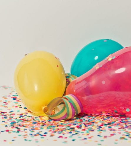 Multicoloured balloons surrounded by confetti