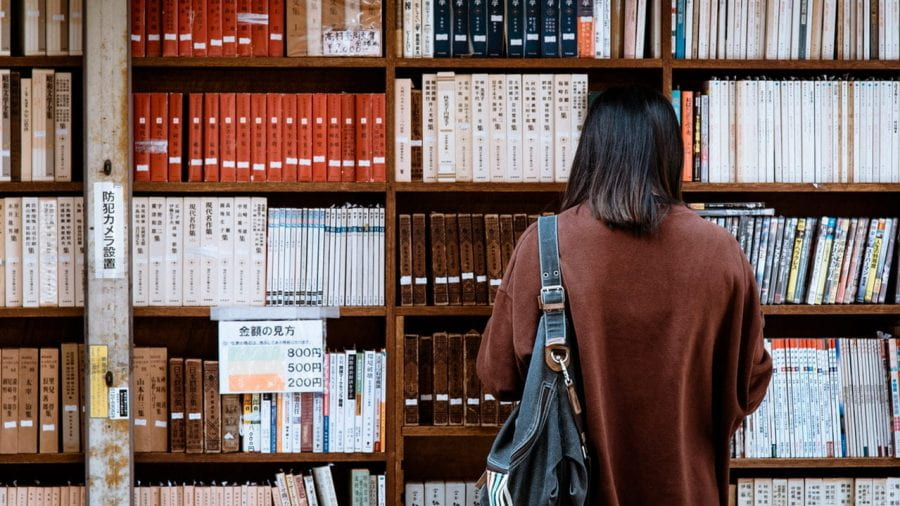 A woman wearing a brown shirt stands in front of a bookcase full of books