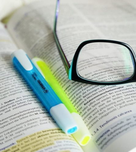 A pair of glasses and two highlighters rest on an open book