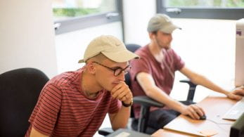 Image of two male students working on computers