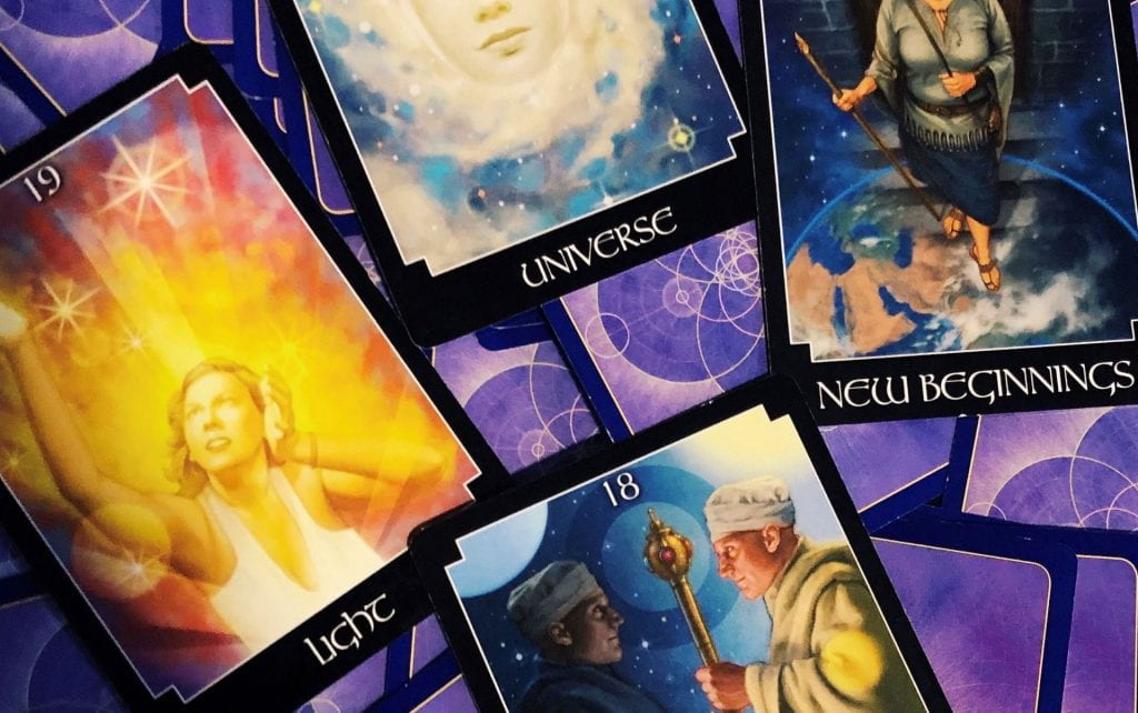 "Selection of tarot cards on a purple backdrop saying ""light"", ""universe"" and ""new beginnings""."
