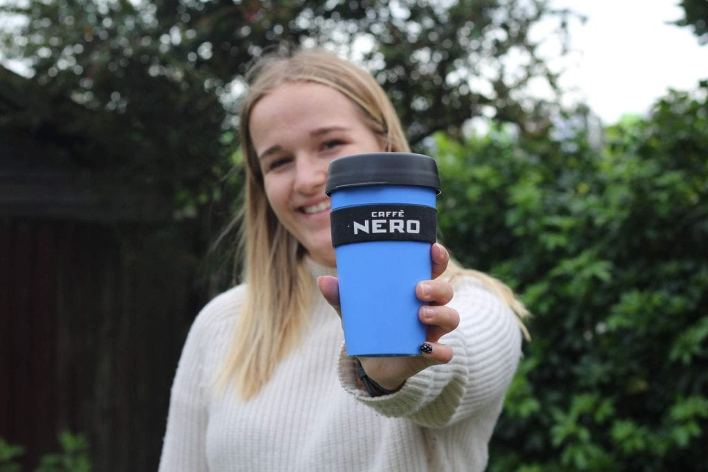 A girl holding a blue Caffe Nero cup towards the camera in a garden.