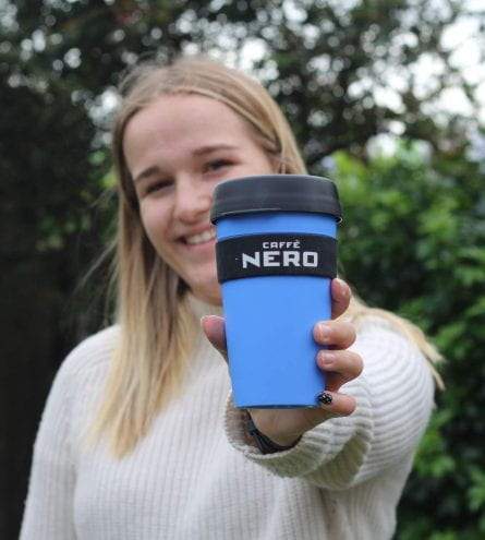 woman smiling and holding caffe nero cup in a park