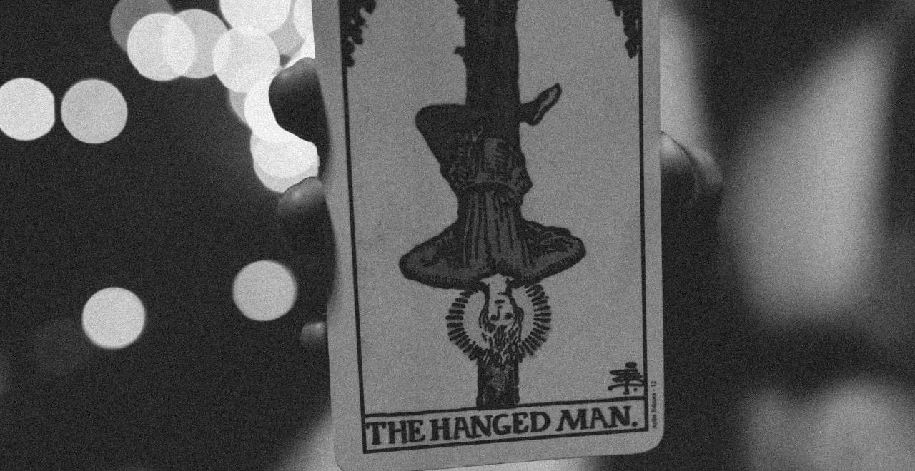 Black and white tarot card depicting the hanged man.