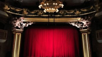 A photo depicting a theatre, with a red curtain closed across the stage.