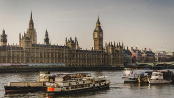 A photo of the parliament buildings in London. Boats can be seen in the river in front.