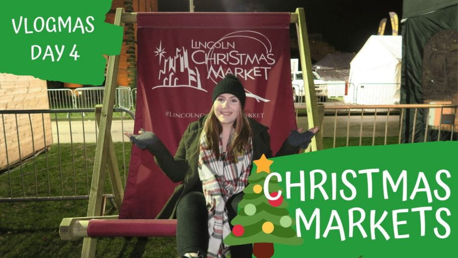 A girl sits on an oversized deck chair at a christmas market.
