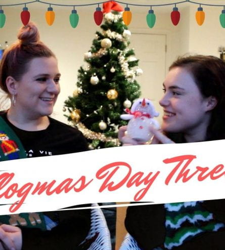 Two girls smiling at eachother. They both have christmas jumpers on.