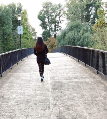 woman walking over bridge surrounded by a lamp post and trees