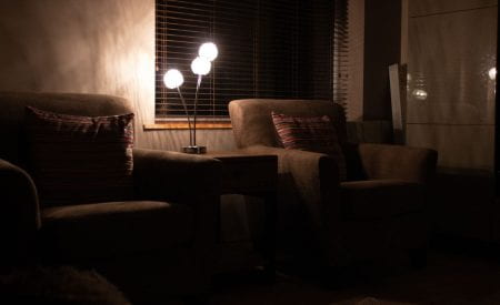 dim lit room with two armchairs with pillows on them