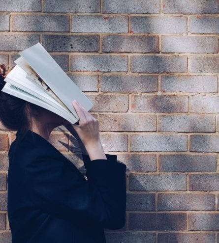 woman putting her head into a book