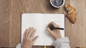 a woman wearing rings, eating a croissant and having a coffee writing in her planner