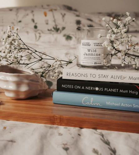 Pile of books, flowers and a candle