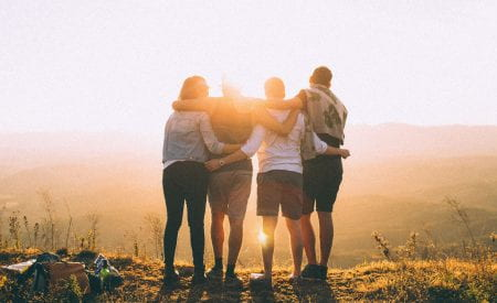 Four people linking arms looking at sunset.