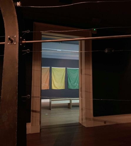 photograph of the electric fence exhibition, featuring the LGBTQI+ flags in the background