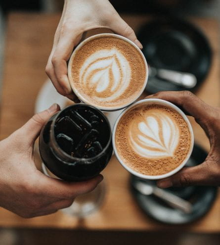 Three people holding their drinks together. Two are regular coffees, and one is an iced coffee.