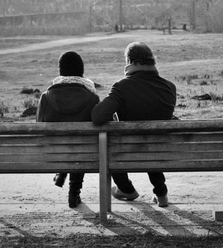 two people sat on a bench in a park, black and white
