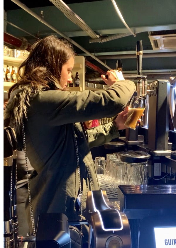 Woman Learning how to pour the perfect pint at the Guinness Storehouse
