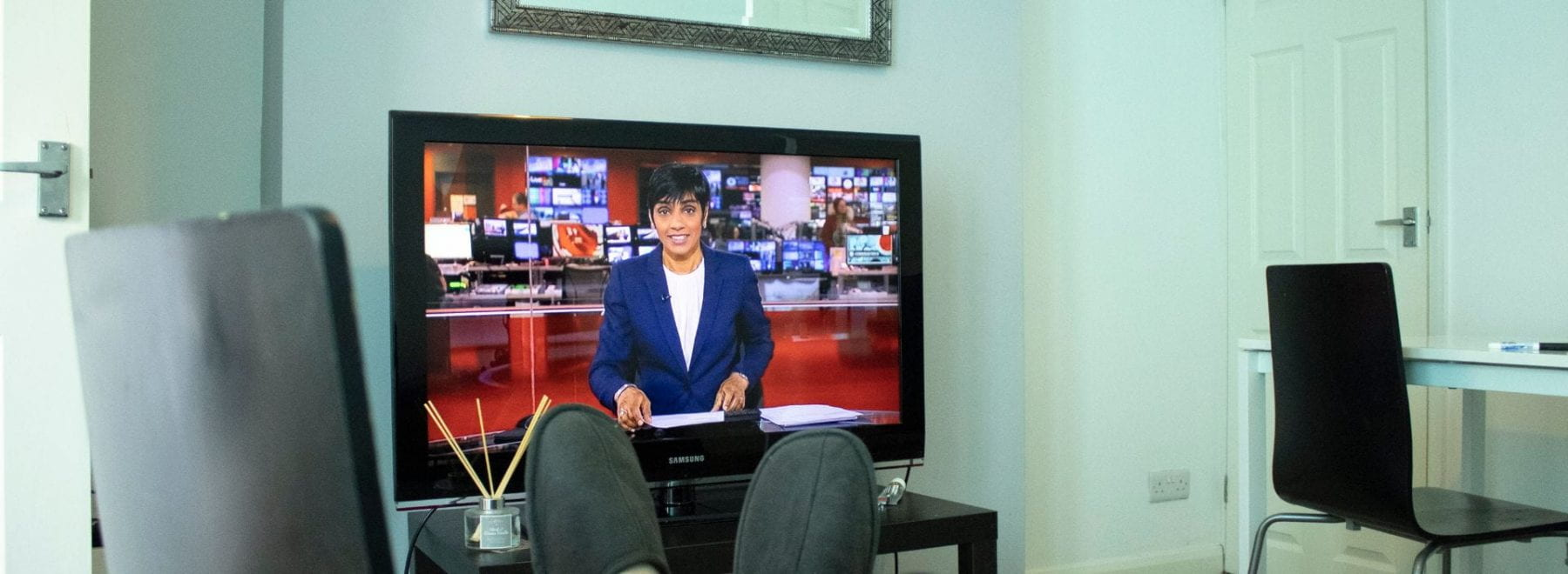 A man with his feet up whilst watching BBC news.