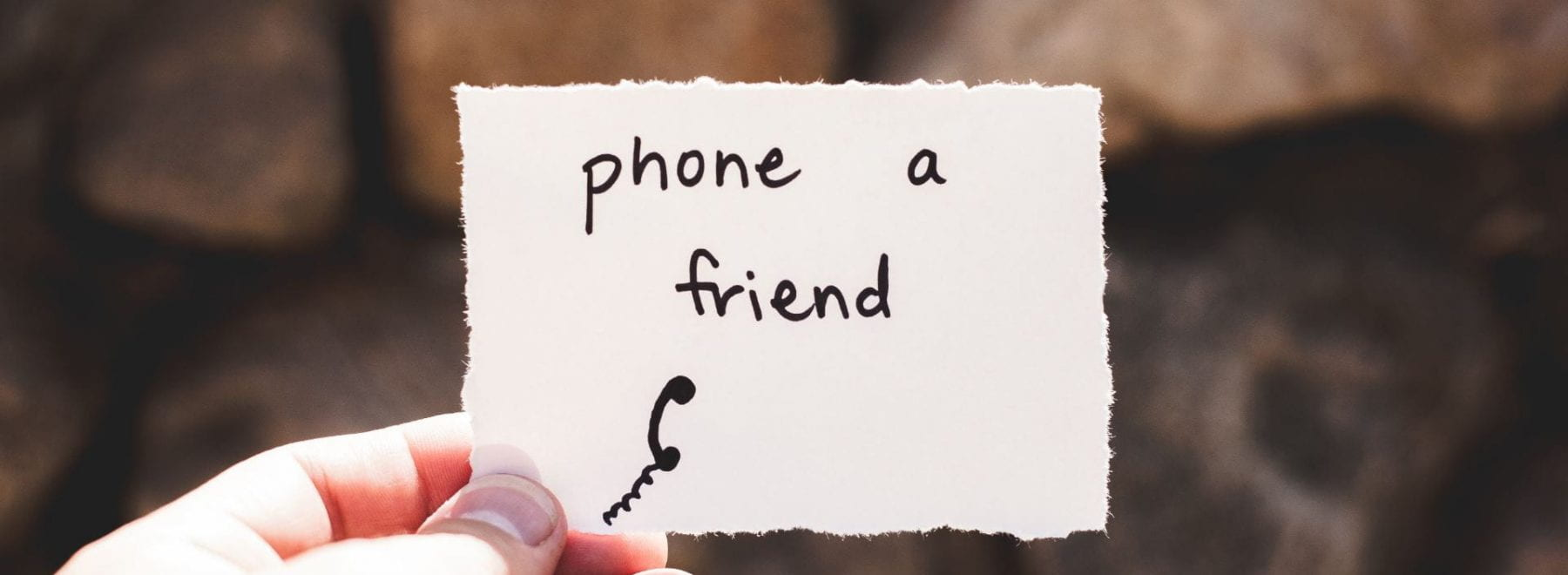 person holding a piece of paper with 'phone a friend' written on it