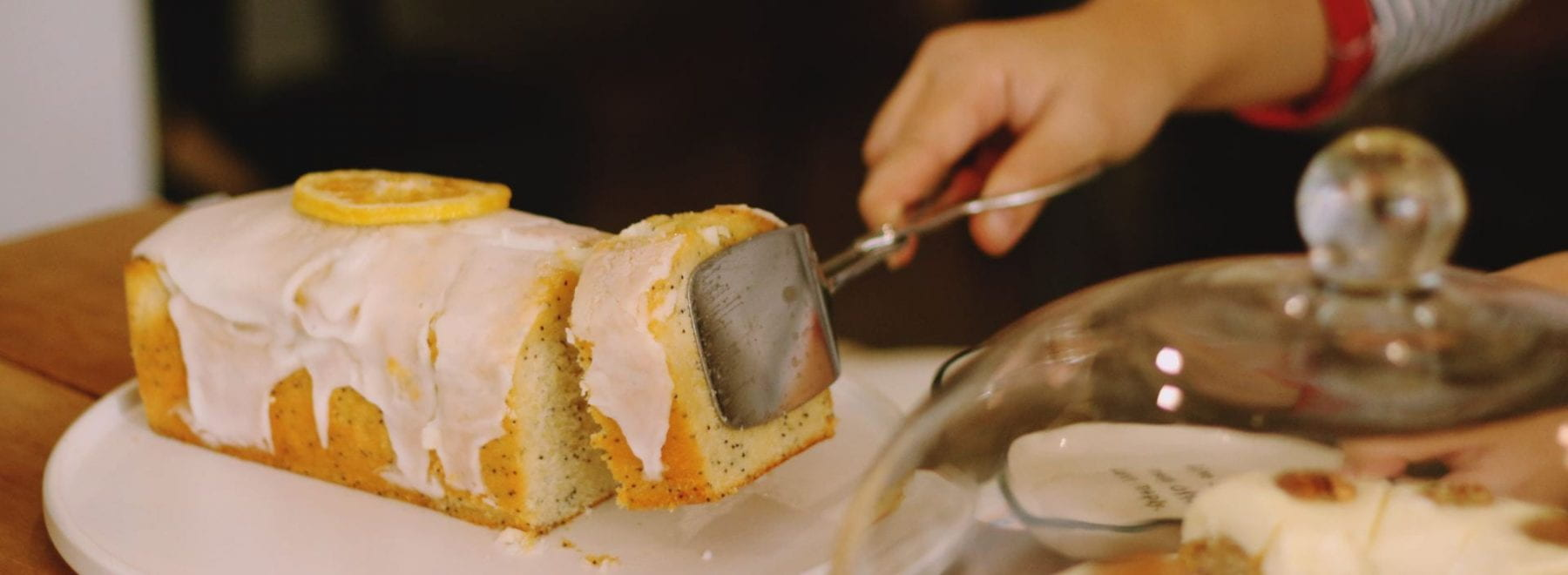A person picking up a slice of lemon cake