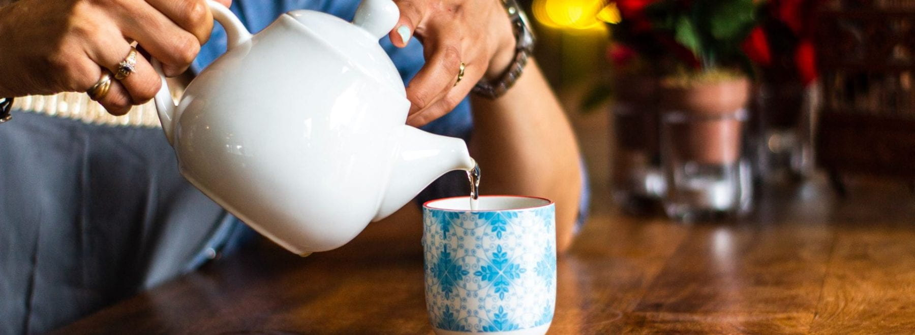 A lady pouring tea from a teapot into a mug