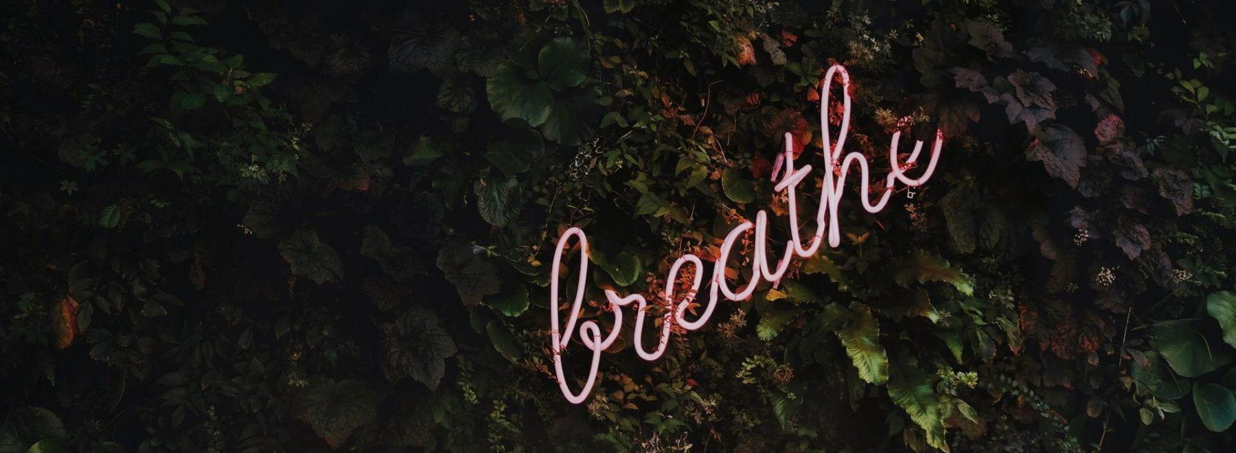 neon sign saying 'breathe'