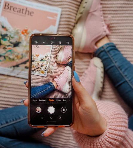 Hand holding phone taking photo