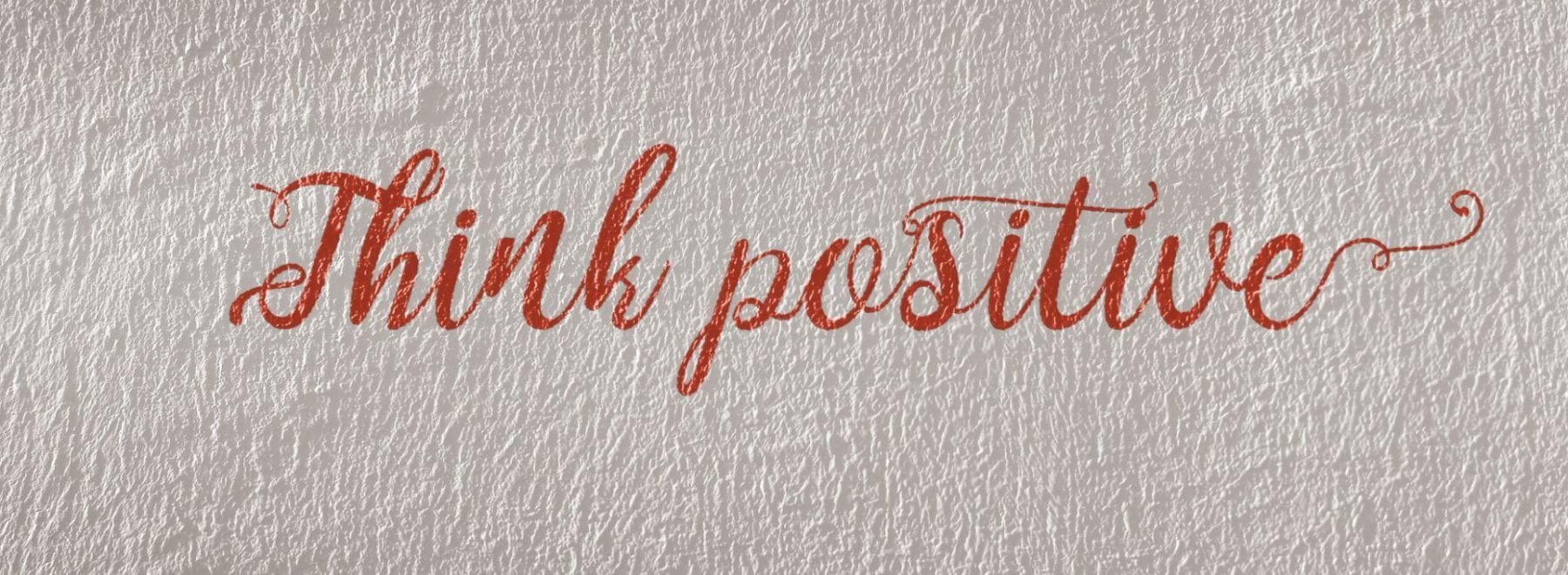 Piece of paper that reads think positive, in red pen