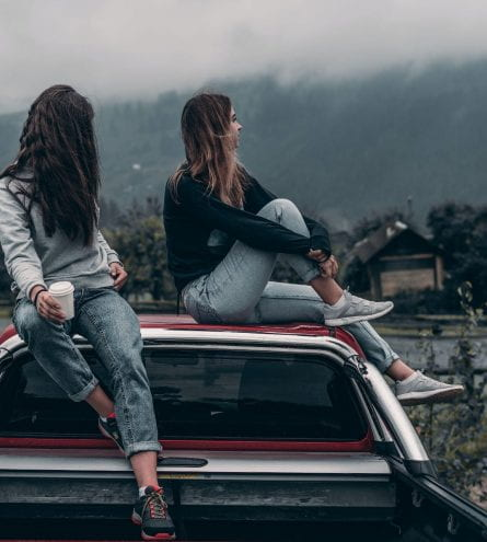 Two women sitting on car roof