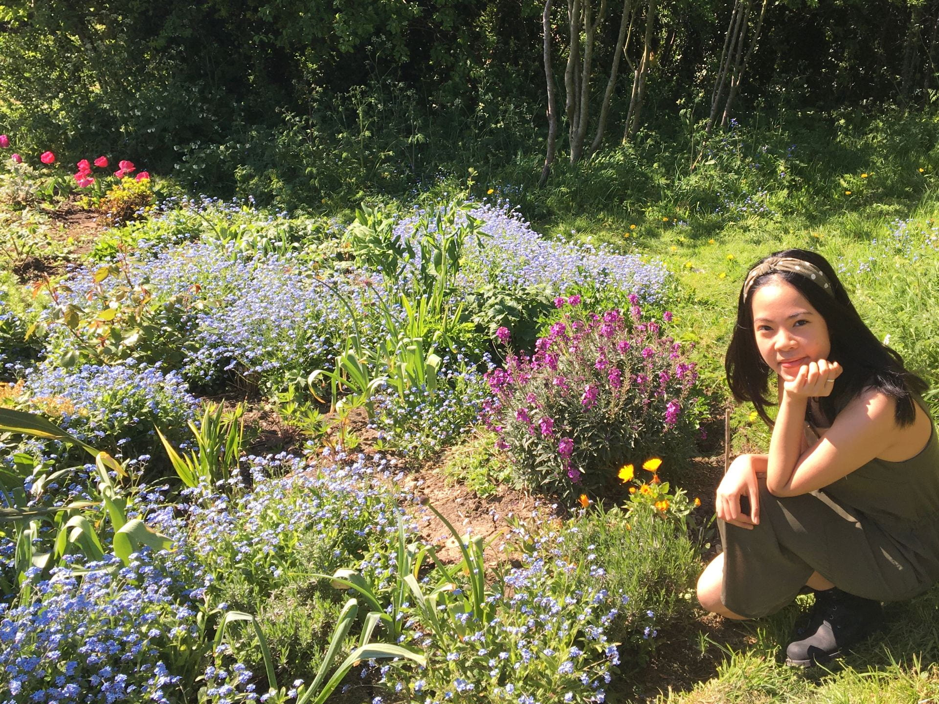 A girl smiling whilst sat in a garden