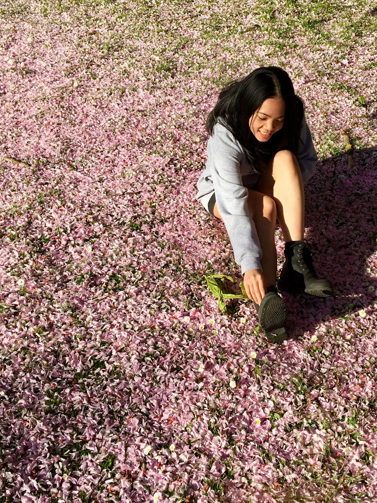 A girl sat in flowers smiling